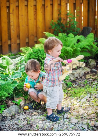 A boy picks up golden Easter eggs during an egg hunt while his little brother plays with a plush toy bunny rabbit outdoors in a garden.  Part of a series. - stock photo
