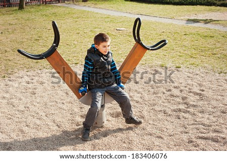 A boy playing in playground area - stock photo