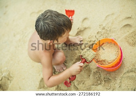 A boy playing on the beach with sand - stock photo