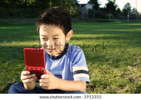 A boy playing video game at a park