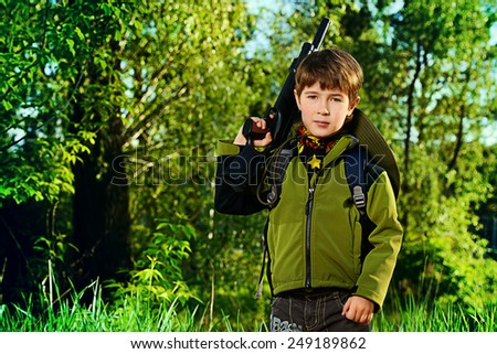 A boy playing with a toy rifle outdoor. Military concept. Childhood. - stock photo