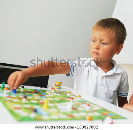 A boy playing with table game. A little of DOF.  - stock photo