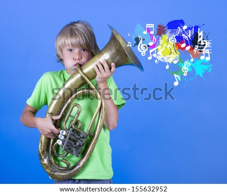 A boy plays the trumpet. - stock photo