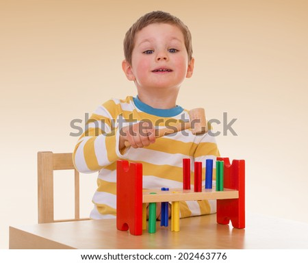 A boy plays with toys, sitting at the table..passionate child for interesting occupation,active lifestyle,happiness concept,carefree childhood concept. - stock photo