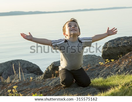A Boy pray at the sunset closer to the beach - stock photo