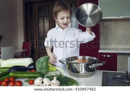 A boy prepares vegetables. Smiling boy with ladle and pan. - stock photo