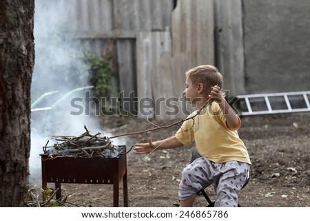 A boy preparing barbecue at the backyard - stock photo
