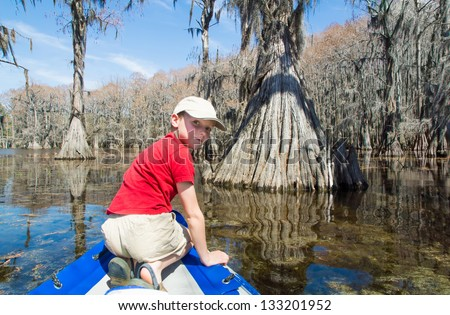 "A boy rides on an inflatable boat of cypress. State Park ""Caddo Lake"", Texas, USA - stock photo"