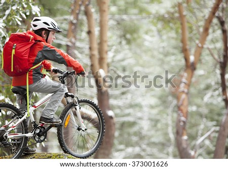 A boy riding his bike in a forrest - stock photo