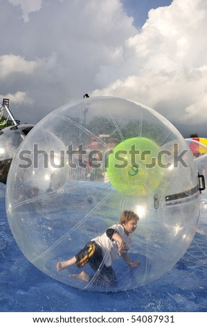 A boy rolling in an inflatable bubble - stock photo