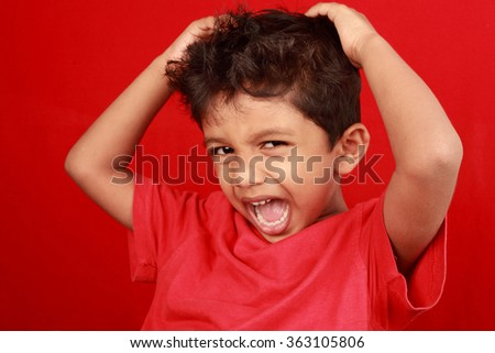 A boy screams loud with mouth wide open in a red background - stock photo
