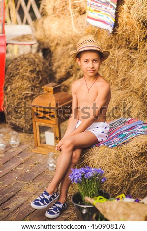 A boy sits among hay decoration, outdoor. Happy boy sitting on hay near flowers in countryside.