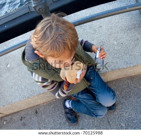 A boy sits on the sidewalk and eat Hotdog - stock photo