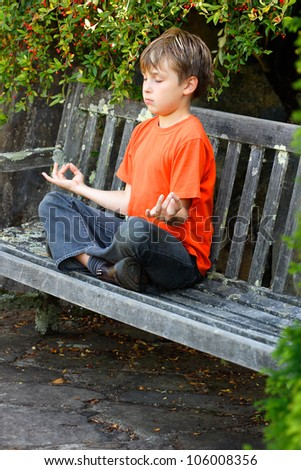 A boy sitting cross legged in yoga zen meditation - stock photo