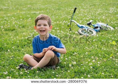 A boy sitting in the grass outside, laughing and smiling. He is wearing a blue shirt. Spring day. Horizontal. He left his bike behind him.  - stock photo