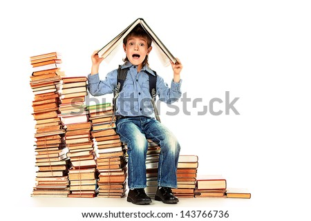 A boy sitting on a pile of books and holding a book on his head. Education. Isolated over white. - stock photo