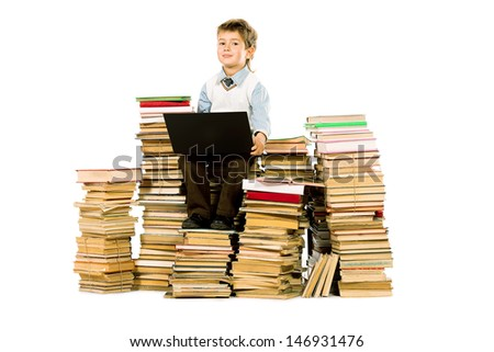 A boy sitting on a pile of books with a laptop on his knees. Education. Isolated over white.