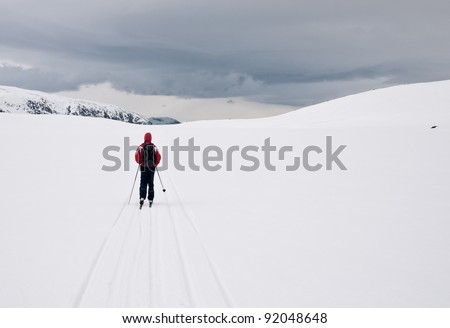 A boy skiing alone on a cloudy day in the norwegian mountains - stock photo