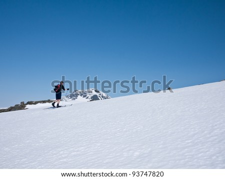 A boy skiing alone up hill at easter in the norwegian mountains