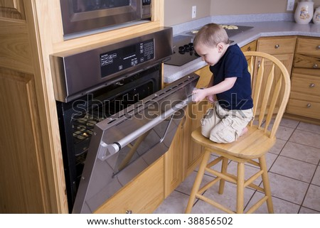 A boy sneaking a peek into the oven at the cookies.