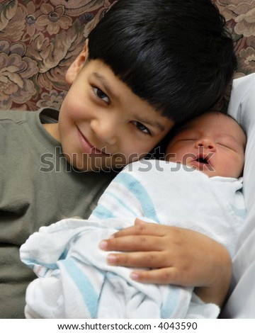 A boy snuggling with his newborn brother at the birthing center. - stock photo