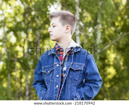 A boy stands in the park and looks into the distance