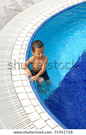 A boy takes a break at the side of swimming pool - stock photo