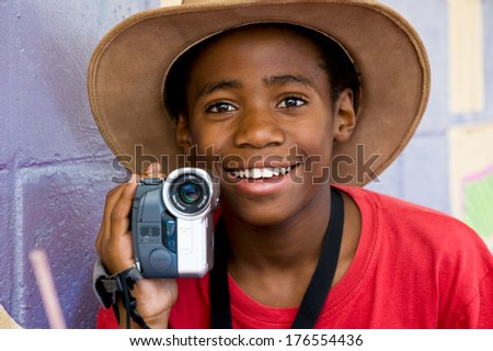 A boy taking videos with a camera he is holding. - stock photo
