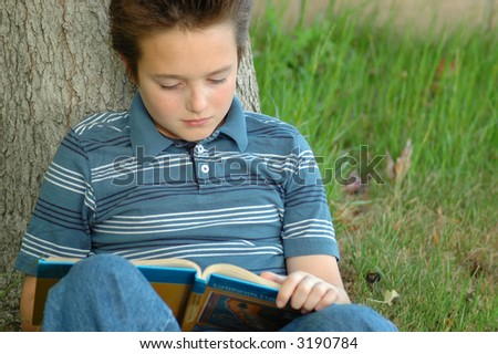 A boy totally immersed in his book while sitting underneath an old tree in the park - stock photo