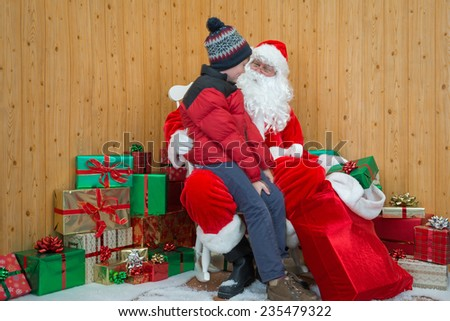 A boy visiting Santa in his grotto at Christmas. - stock photo