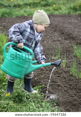 A boy watering soil - stock photo