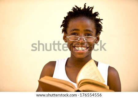 boy wearing glasses holding an open book. - stock photo