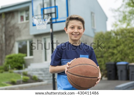 A Boy with a ball outside in fron of his house - stock photo