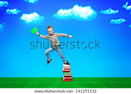 A boy with a book in hand is flying to knowledge. Educational concept. - stock photo