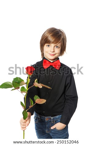 A boy with a red rose in her hand standing on white background - stock photo