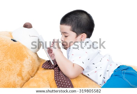 A boy with a tablet on a  teddy bear,on  white background.