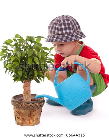 a boy with a watering-can is giving the flowers some water - stock photo
