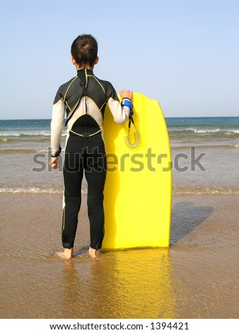 A boy, with its body board, is evaluating the surf - stock photo