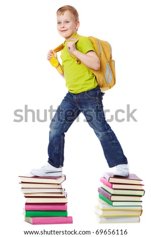 A boy with satchel walking on two heaps of books - stock photo