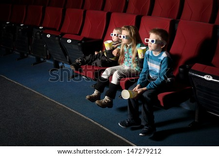 A boy with sister and small brother in 3D glasses watching a movie on the front row of the cinema - stock photo