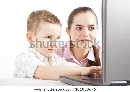 A boy with young woman are working with the laptop. The boy uses of computer. He is learning, maybe plays on game. She's watching what he does. - stock photo