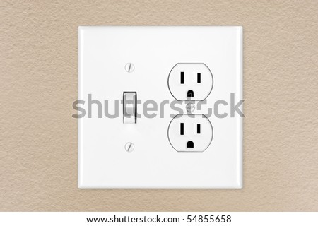 A brand new modern electrical toggle light switch and power outlet on a freshly painted wall. - stock photo