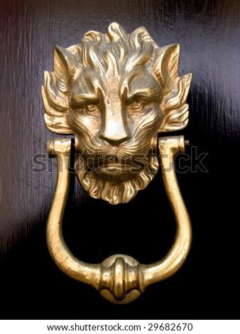 A brass door knocker in the shape of a lion's head on a black wooden door - stock photo