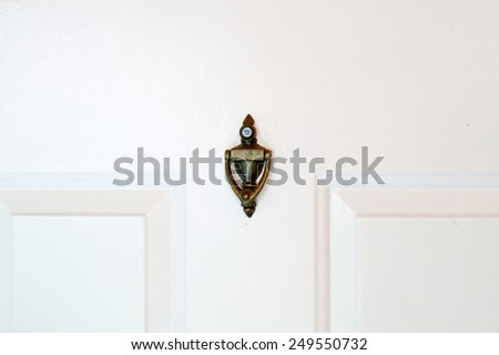 A brass door knocker with peep hole in the middle of a white door. - stock photo