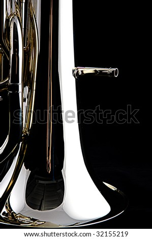 A brass gold bass tuba euphonium isolated against a black background in the vertical format with copy space.