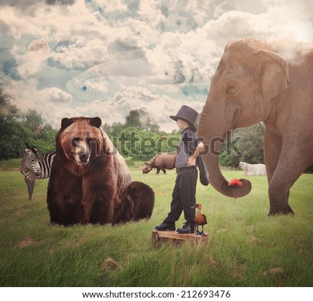 A brave child is standing in a nature field with wild animals around him such as a bear, elephant, zebra and bear for an imagination or creative concept. - stock photo