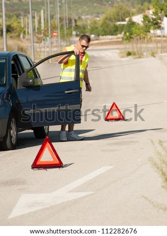 A breakdown on a lonely road  and a fed up driver - stock photo