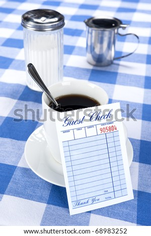 A breakfast and coffee setting in a cafe diner with a blank check for placement of copy. - stock photo