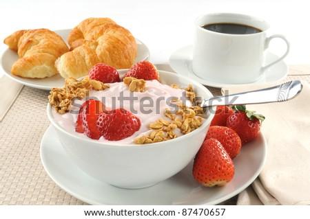 A breakfast of croissants, yogurt, strawberries and black coffee - stock photo