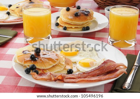 A breakfast with bacon and fried eggs with blueberry pancakes and orange juice - stock photo